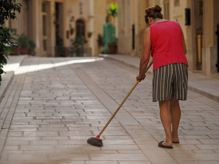 Rear view of woman sweeping alley amidst buildings in town