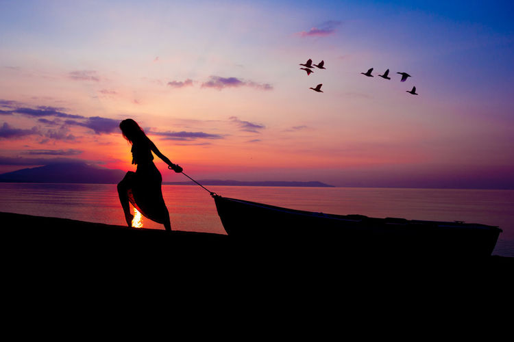 Portrait of a girl with the little boat Beach Beauty In Nature Bird Day Flying Horizon Over Water Leisure Activity Lifestyles Men Nature One Person Outdoors People Portrait, Real People Scenics Sea Silhouette Siluete Sky Sunset Water