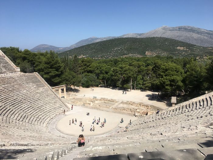 People at the great theatre of epidaurus on sunny day