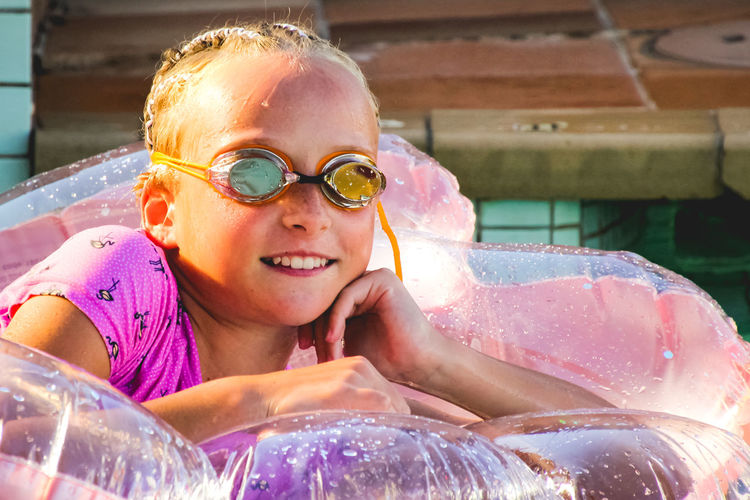 portrait of a young girl relaxing in the pool on pink inflatable Summertime Pink Color Swimming Pool Swimming Goggles Vacations Happiness Smiling Headshot One Person Portrait Lifestyles Emotion Front View Childhood Leisure Activity Females Real People Girls Child Looking At Camera Outdoors Fun