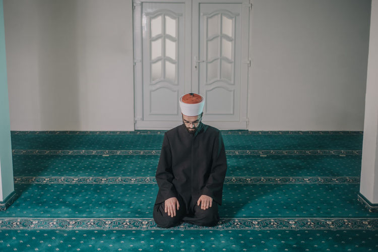 Young man praying in mosque