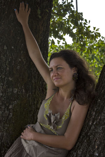 Portrait of smiling young woman against tree trunk