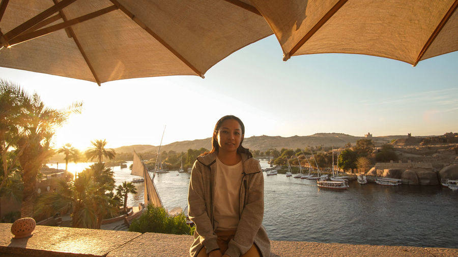Asian tourist at beautiful sunset of nile river bank scene in aswan egypt
