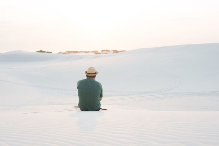 Rear View Of Man Sitting On Sand Dune Against Clear Sky