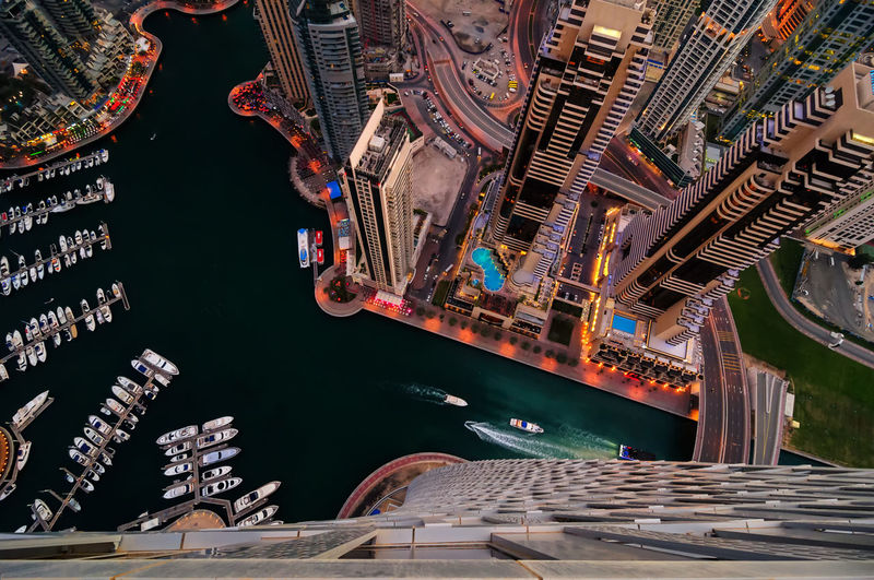 Aerial view of boats at harbor by modern buildings in city