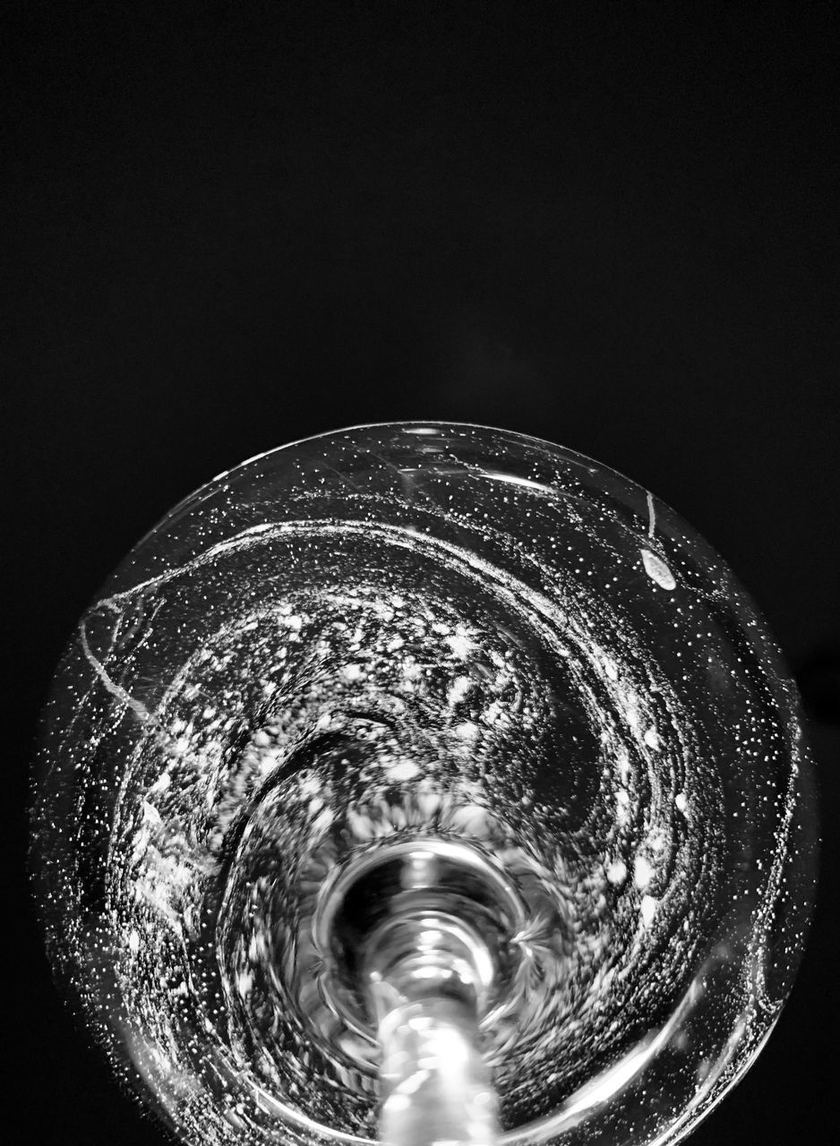 CLOSE-UP OF WATER DROPS ON METAL AGAINST BLACK BACKGROUND