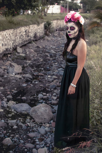 Full length of woman with make-up standing by rock outdoors
