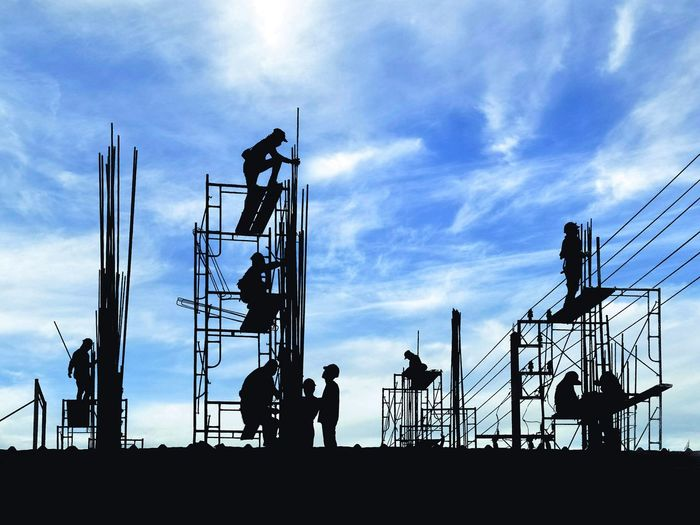 Silhouette construction workers group are working to build reinforcement structure on top of building with blurred clouds and blue sky background in industrial concept Silhouette Occupation Reinforcement Infrastructure Working Outdoor High Team Group Blue Sky Clouds Bright Shadow Steel Materials Hardhat  Headwear Manual Worker Occupation Industry Silhouette Industrial Equipment Working Scaffolding Construction Site Building - Activity Incomplete Construction Worker Worker Construction Equipment