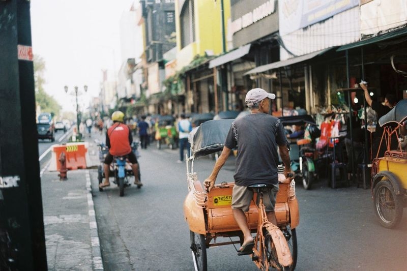 """Pedicab driver and in Indonesian we called """"becak"""". I shot this pic with Olympus OM-1 camera and used Kodak ColorPlus 200 film. City Street Transportation Mode Of Transportation Building Exterior Architecture Men Land Vehicle City Life Built Structure Road People Rear View Incidental People Day Occupation Outdoors Traditional Cultures Javanese INDONESIA Film Photography Filmisnotdead Analogue Photography Kodak EyeEmNewHere"""