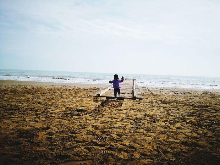 Girl running on pier at beach