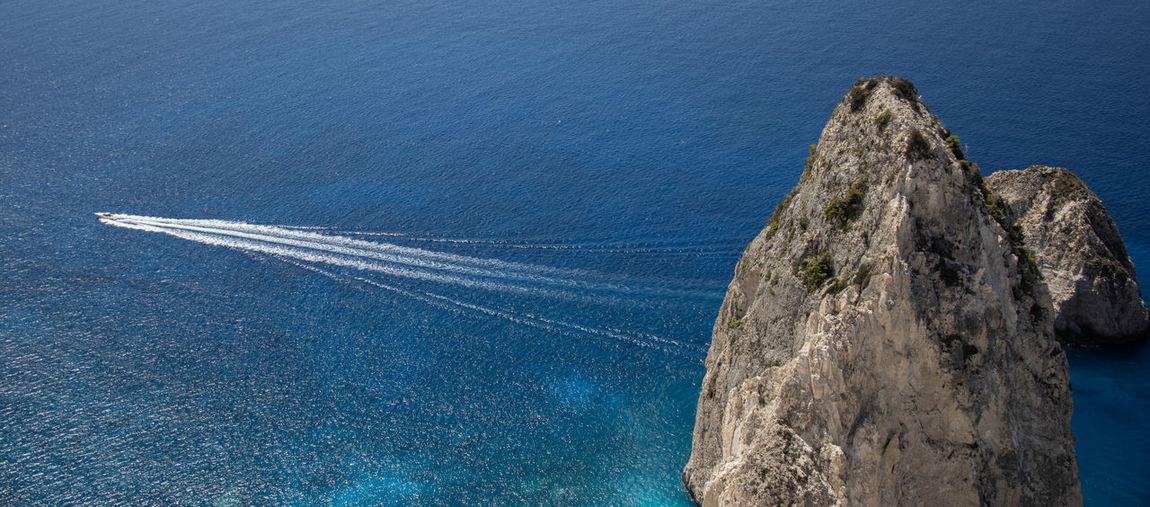 Aerial view of rocks by sea against blue sky