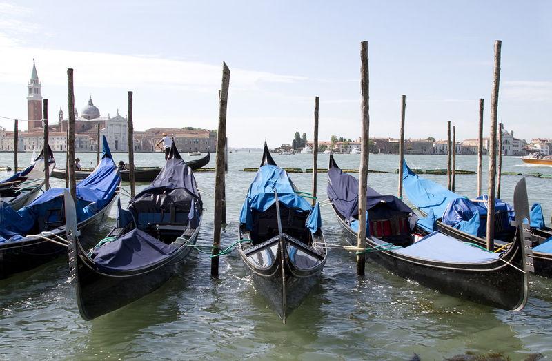 Gondolas moored at venetian lagoon against sky