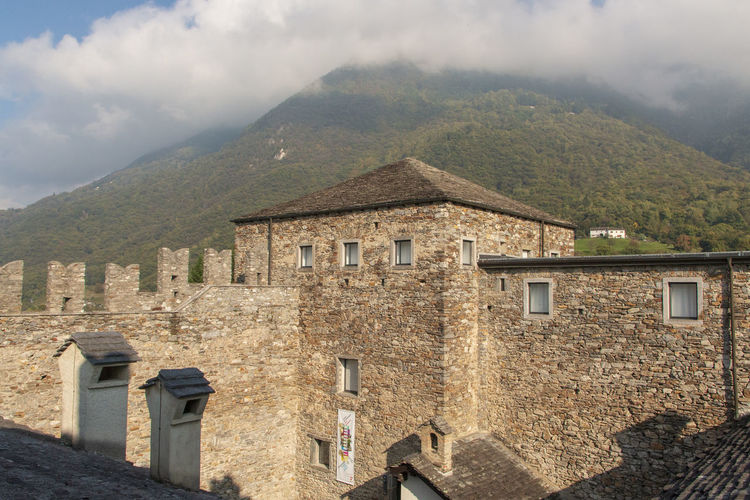 Old building by mountains against sky