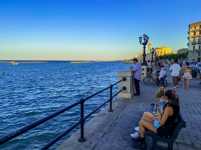 People sitting on railing by sea against sky