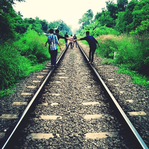 Rear view of people walking on railroad track