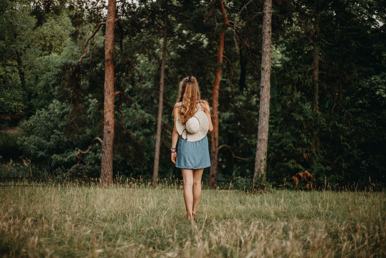 Rear View Of Woman Walking On Grassy Field In Forest