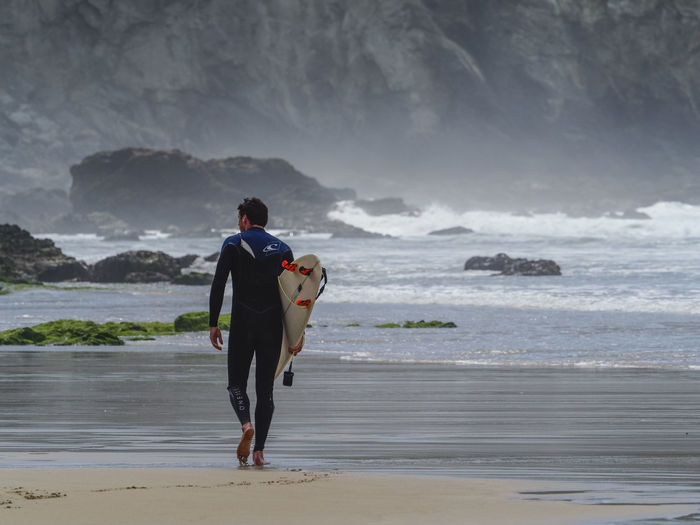 Rear View Of Surfer Carrying Surfboard While Walking On Shore At Beach