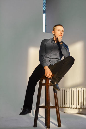 Young man looking away while sitting on chair against wall