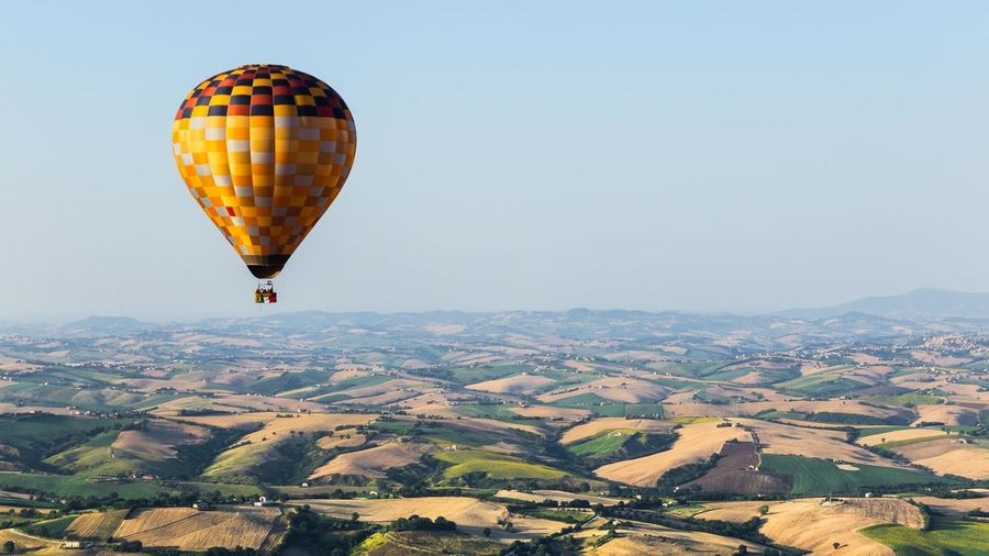 Hot air balloon flying above landscape against clear sky