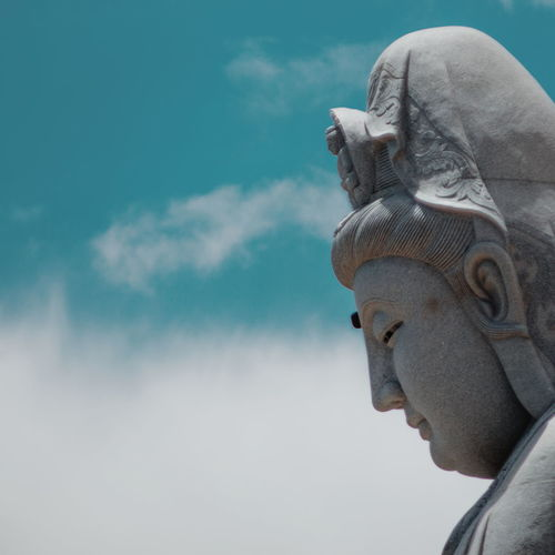 Close-Up Side View Of Buddha Statue Against Clouds