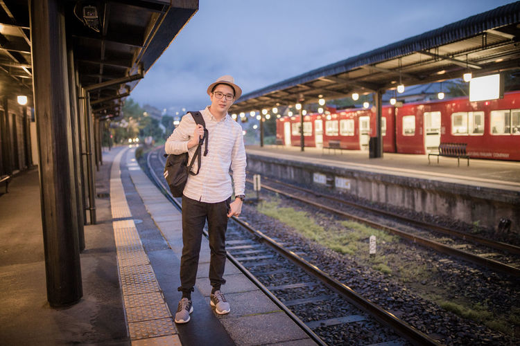 Portrait Of Mid Adult Man With Backpack Standing At Railroad Station Platform Against Sky