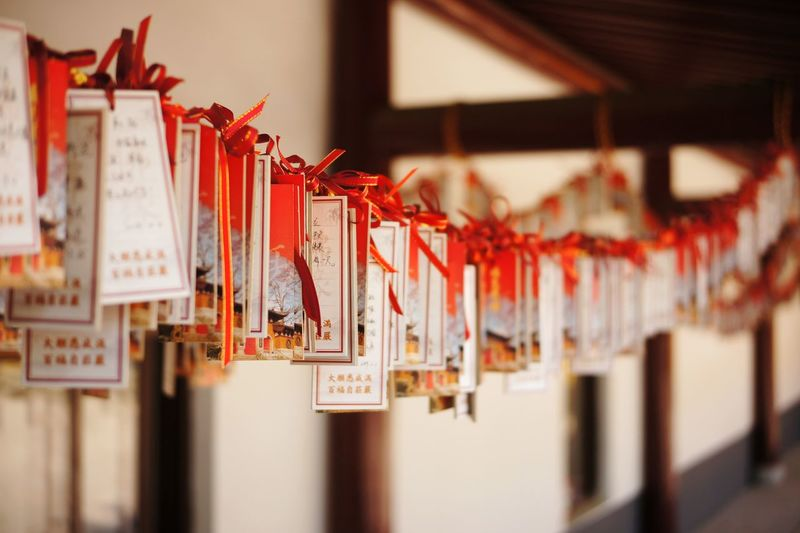 Close-up of fortune papers hanging in temple