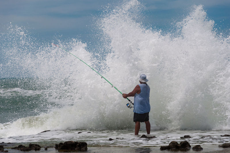 Full length of man fishing in sea at shore