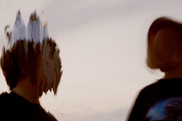 Close-up rear view of couple against sky during sunset