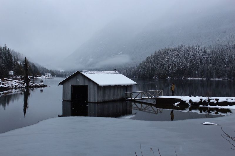 Boathouse by lake against sky during winter