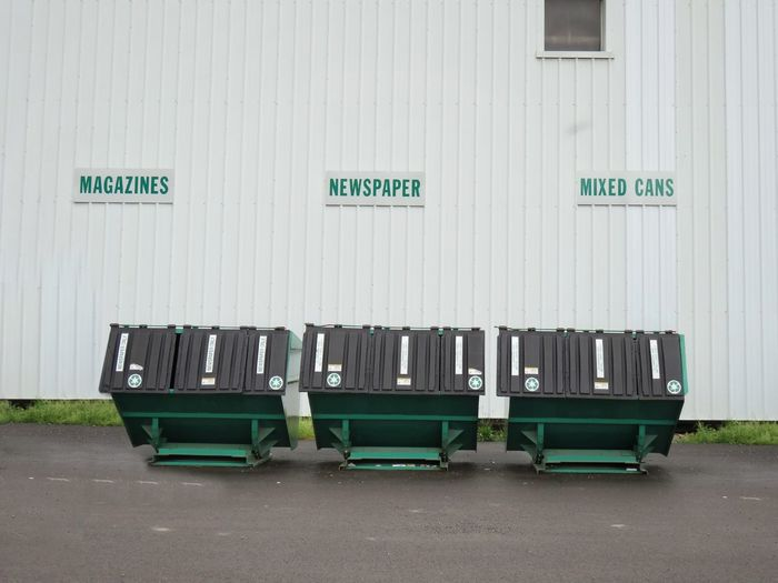 Row of recycling bins against exterior wall