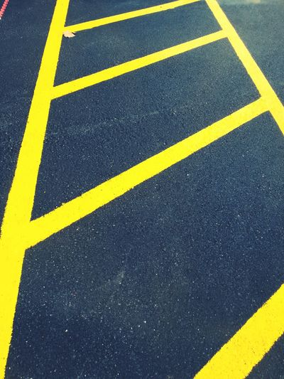 High angle view of yellow road marking at parking lot