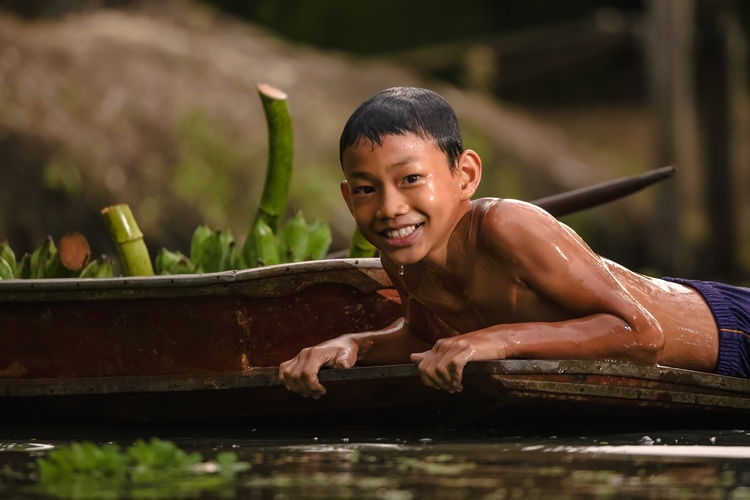Portrait of smiling shirtless boy lying on boat in river