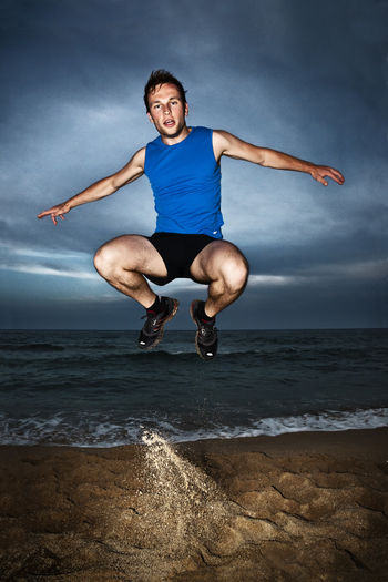 Full length of young man jumping on beach