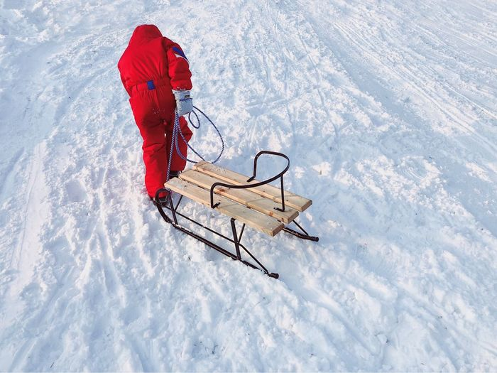 High Angle View Of Person Pulling Sled On Snow Covered Field