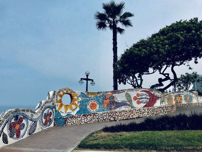 Graffiti on wall by palm trees against sky