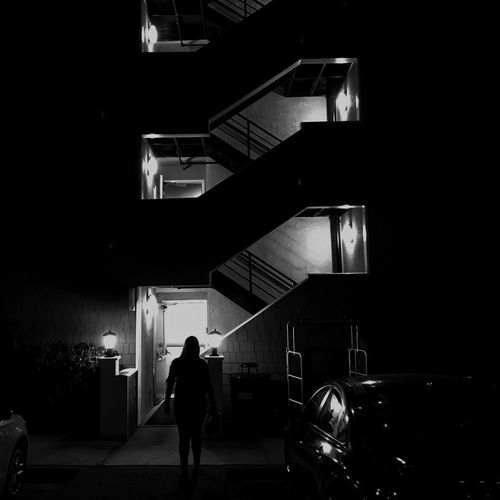 Rear view of silhouette man walking in illuminated building at night