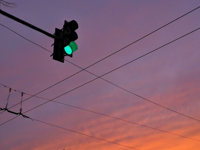 Low Angle View Of Illuminated Stoplight Against Sky During Sunset
