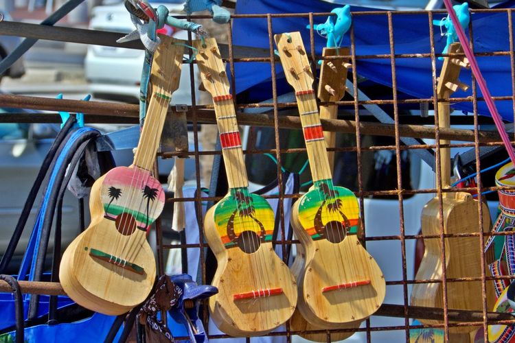Musical Instrument No People Hanging Music Choice Musical Equipment Focus On Foreground Large Group Of Objects Wood - Material Outdoors Arts Culture And Entertainment String Instrument Still Life Art And Craft Multi Colored Variation Creativity Guitars