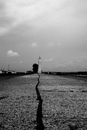 Silhouette man standing in water against sky
