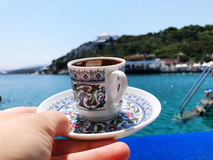 Turkish Coffee Turkey Summer Beach Sea EyeEm Selects Human Hand Hand Food And Drink Drink Cup Human Body Part One Person Refreshment Real People Mug Holding Close-up Coffee Day Focus On Foreground Coffee - Drink Personal Perspective Coffee Cup