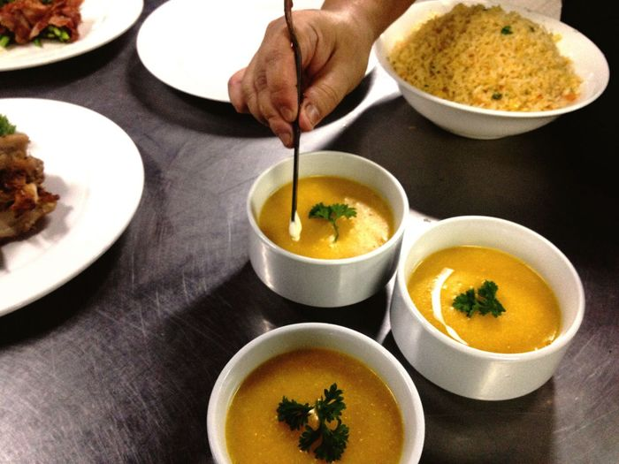 Cropped image of chef garnishing squash soup at restaurant