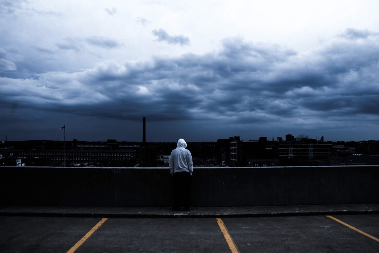 Rear view of man standing on road against cloudy sky
