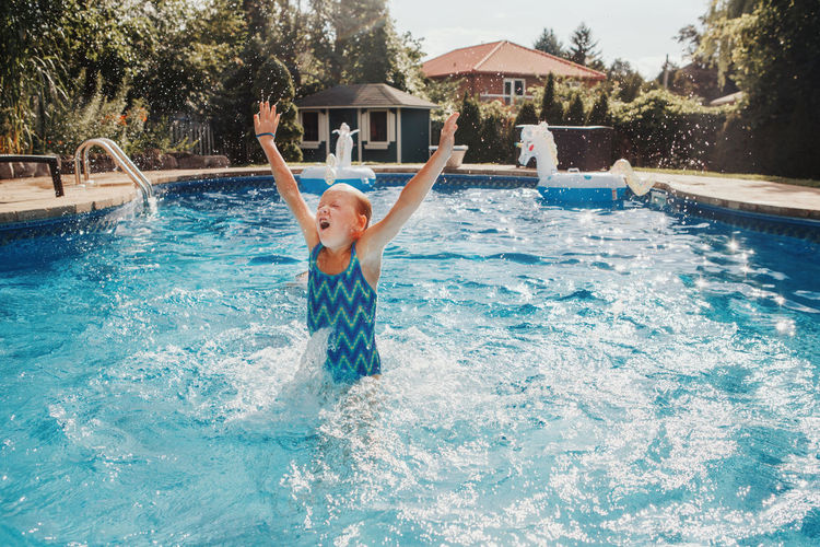 Girl swimming splashing in pool on home backyard. summer outdoor water activity for kids.