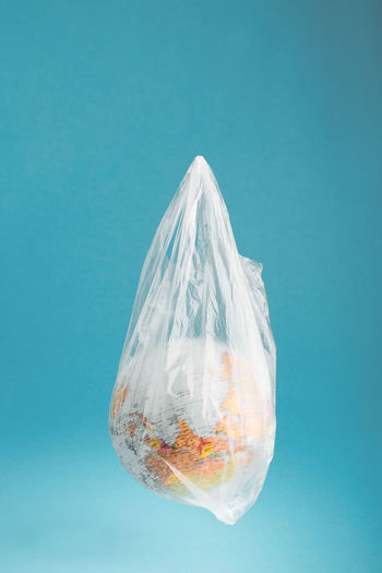 Close-up of globe in plastic bag against blue background