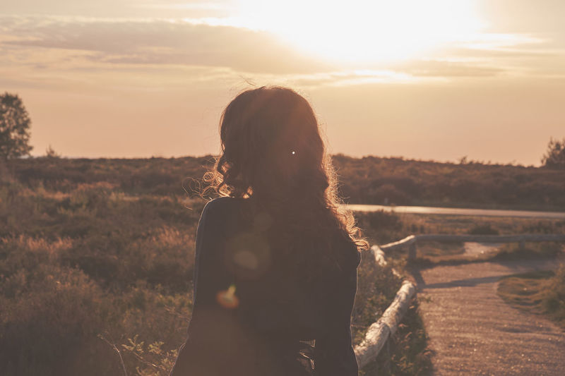 Beauty In Nature Child Childhood Field Hairstyle Land Landscape Leisure Activity Lens Flare Lifestyles Nature One Person Outdoors Real People Rear View Scenics - Nature Sky Standing Sunlight Sunset Waist Up Women