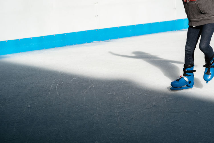 Low Section Of Person Ice-Skating On Rink
