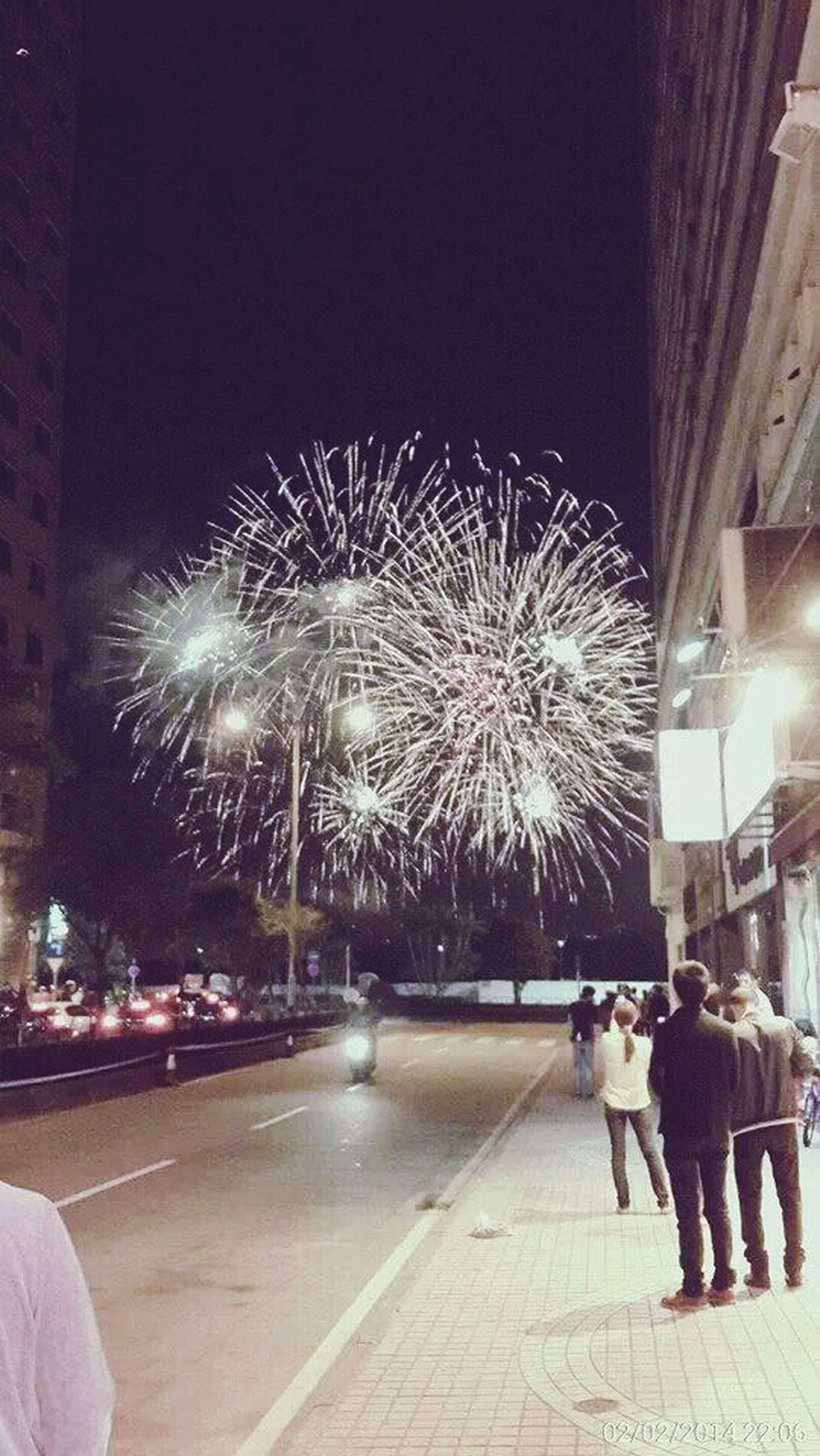 illuminated, night, arts culture and entertainment, celebration, lifestyles, leisure activity, men, firework display, large group of people, person, motion, event, building exterior, exploding, architecture, long exposure, built structure, sparks, city