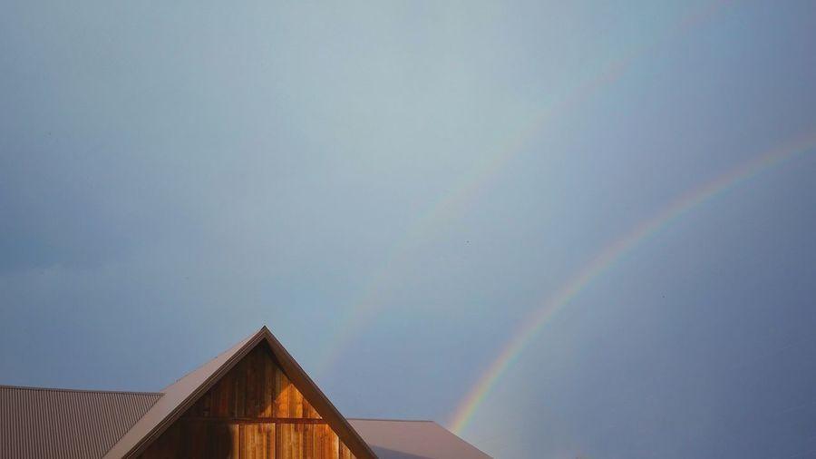 Rainbows over house against clear sky