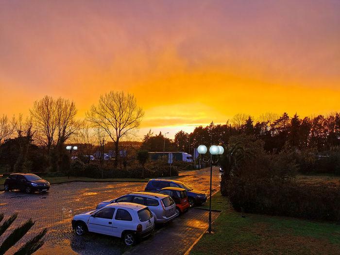 Cars parked on road against orange sky