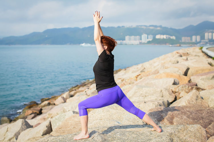 Woman doing yoga on rock by sea